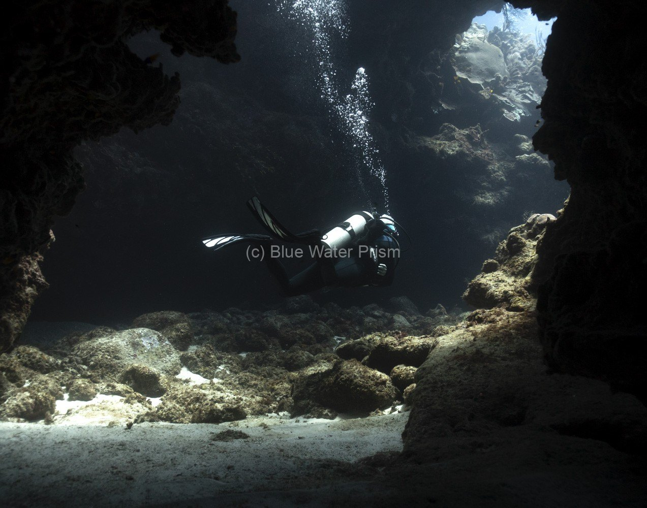 Diver going through swim through in Grand Cayman