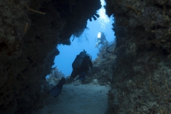 Diver going through swim through in Cozumel